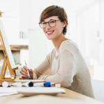 Portrait of smiling woman painting at easel on table
